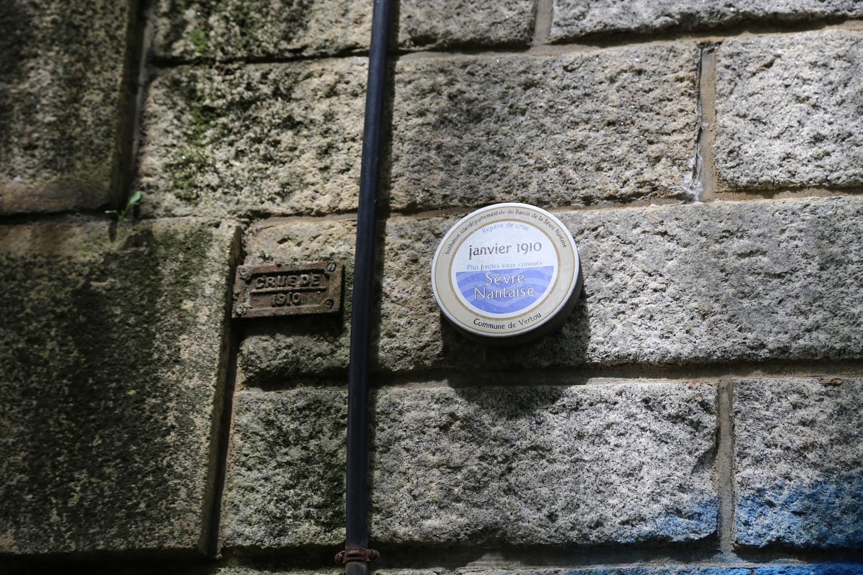 Deux repères de crue côte à côte: à gauche une plaque non officielle, à droite un macaron officiel